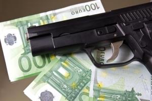 Gun lying on 100 euro banknotes