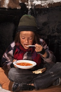 Poor beggar child eating charity food