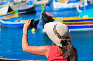 tourist making photo of colorful traditional boats in Malta
