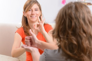 Smiling deaf woman learning sign language and talking with her teacher