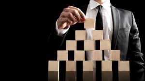 Close Businessman Arranging Small Wooden Plain Blocks to a Pyramid Figure on Black Background. An Imaginative Business Hierarchy Concept.