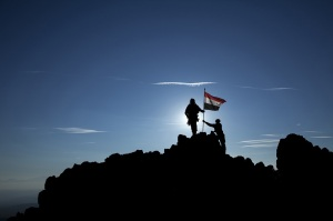 Two soldiers raise the Syrian flag on top of the mountain