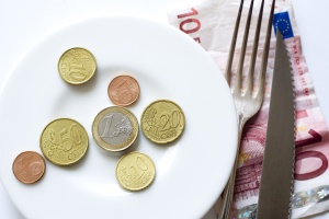 Plate with various euro coins, fork and knife lying on 10 euro banknote.