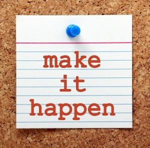 The words Make It Happen in red text on a note card pinned to a cork notice board as a reminder and for motivation