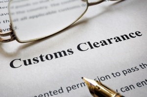 Page of paper with words Customs Clearance and glasses.