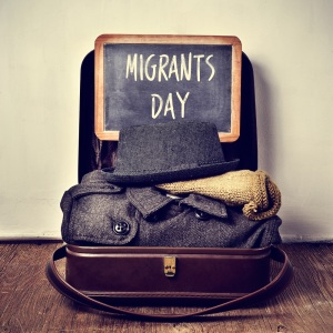 old suitcase with some clothing and chalkboard with text migrants day