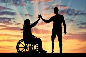 A silhouette of a woman in a wheelchair and a man with a prosthetic leg standing to support each other. The concept of people with disabilities