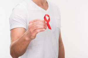 Man in white t-shirt holding a red AIDS ribbon