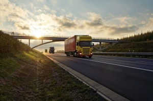 Trucks passing under a concrete bridge on the asphalt road at sunset.