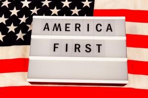 Lichtbox mit Buchstaben - AMERICA FIRST - auf einer amerikanischen Nationalflagge