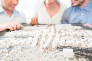 Architects or civil engineers with model for urban development in the office