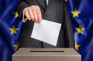 Election in European Union - voting at the ballot box. The hand of man putting his vote in the ballot box. Flag of EU on background.