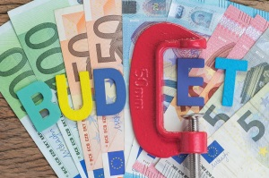 Europe finance, economic, money squeezing idea, colorful alphabet word BUDGET using red clamp as G letter on Euro banknotes on wooden table, crisis and world depression.