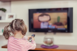 little cute girl is pointing remote to tv to change change channel. There is a shallow depth of field.