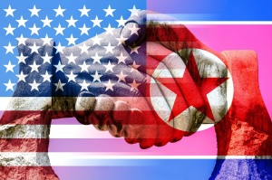 Giant stone handshake shining through the american and north korean flag peace concept