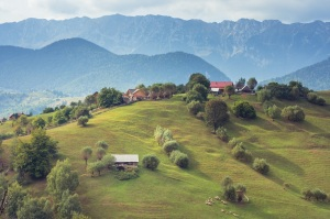 Mountain landscape in Romania. Rural Romanian landscape. Landscape in Magura village and Piatra Craiului Mountains in the background. Traditional Romanian village and mountains panorama.