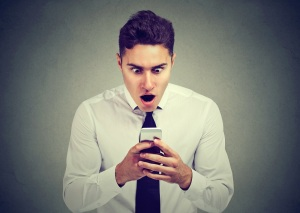Closeup portrait surprised man looking at phone seeing unexpected news or photos with wonder emotion on face