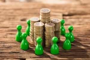 Stack Of Coins Surrounded With Green Figures On Wooden Desk