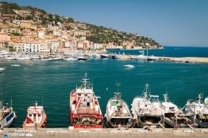 Porto Santo Stefano, Italy - June 24, 2017: Harbor seafront and village skyline, italian travel destination. Monte Argentario, Tuscany, Italy.