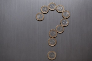 Question mark made of one euro coins on a metallic background. European currency finance concept. Close-up