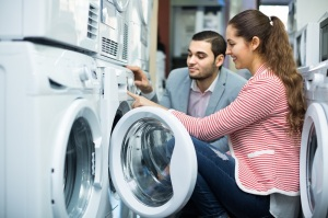Positive salesman and adult customers in store of domestic appliances