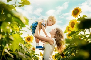 Beautiful mother is tossing up her cute little son in sunflower field. Both are happy. Image with selective focus