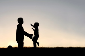 Silhouette of a happy young child smiling as he runs to greet his father with a hug at sunset on a summer day.