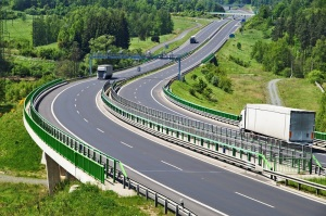 The highway between woods, in the middle of the highway electronic toll gates, three moving trucks, in the distance Bridges