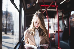 Young woman sitting in city bus and reading a book