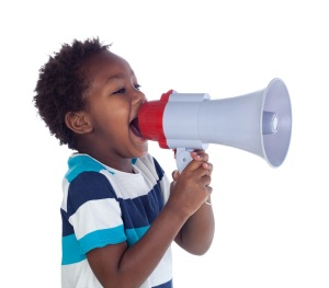 Small boy shouting through a megaphone isolated on white background