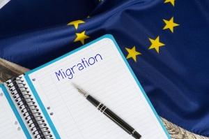 Flagge der europäischen Union EU und ein Schreibblock mit dem Wort Migration
