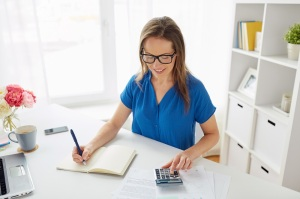 business, finance and accounting concept - middle-aged woman with calculator counting and writing to notebook at office
