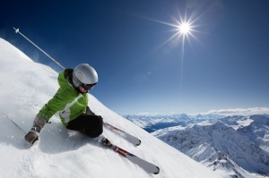 Female skier on downhill race with sun and mountain view.