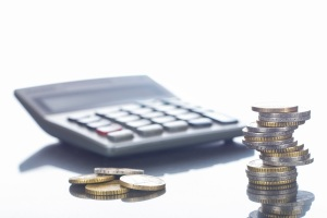 Finanzen, Euro, Euromünzen im Stapel und liegend auf spiegeldem Tisch und Taschenrechner, Hintergrund