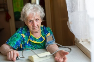 Old woman measures to itself blood pressure.