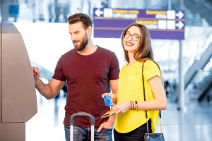 Young couple withdrawing money using ATM at the airport during their travel