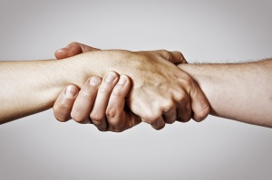 Concept of salvation. Image of the hands of two people at the time of rescue (help).