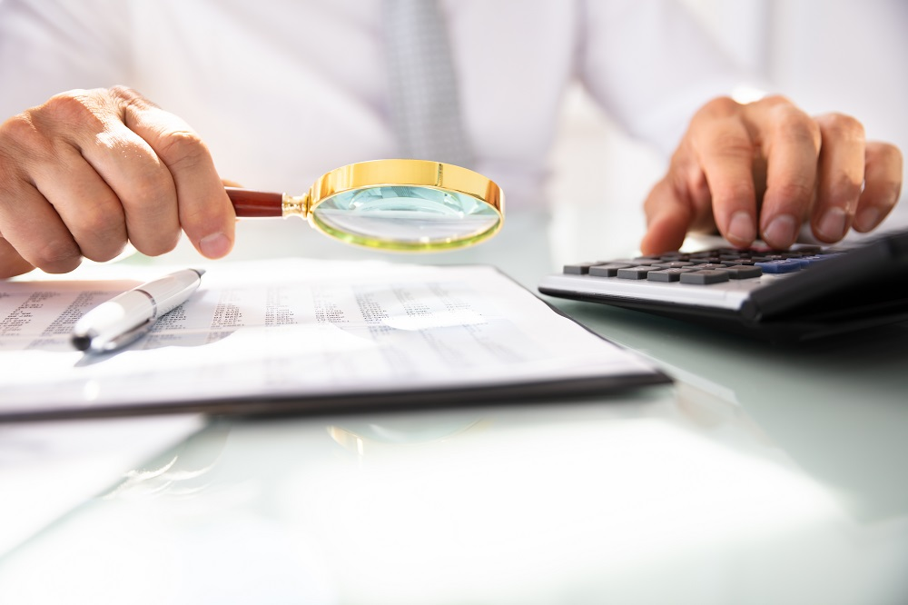 Businessman Analyzing Financial Report With Magnifying Glass