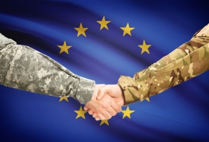 Soldiers shaking hands with flag on background - European Union
