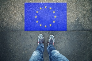 Point of view of a person legs standing in front of EU Flag painted on city asphalt street ground.