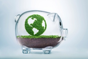 Grass growing in the shape of planet Earth, inside a transparent piggy bank, symbolising the need to invest in the protection of the environment and to reconnect with nature.