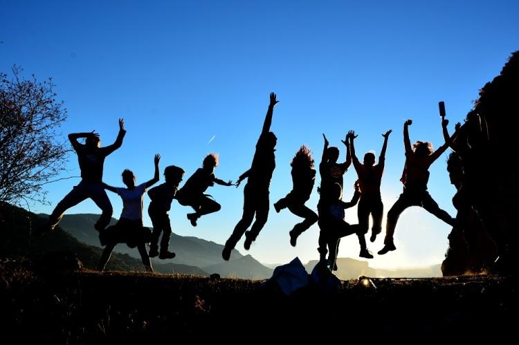 Silueta de amigos saltando en contraluz en lo alto de la montaña