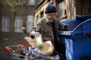 Homeless man searching for empty bottles and other stuff for recycle.