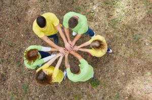 Junge Leute stehen im Kreis und stapeln Hände für Teamentwicklung und Teambuilding