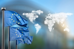 Flags of European Union with world map made of clouds against European Parliament in Brussels, Belgium