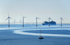 Very large passenger ship and a small sailboat pass offshore wind turbines near the Oresund Bridge between Denmark and Sweden