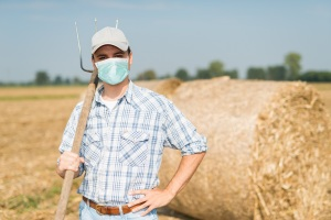 Farmer standing in his field while wearing a mask, coronavirus pandemic concept