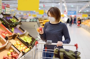 Young woman wearing disposable medical mask shopping in supermarket during coronavirus pneumonia outbreak. Protection and prevent measures while epidemic time.