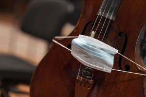 A face mask put over the bridge of a cello representing performance restrictions during a pandemic