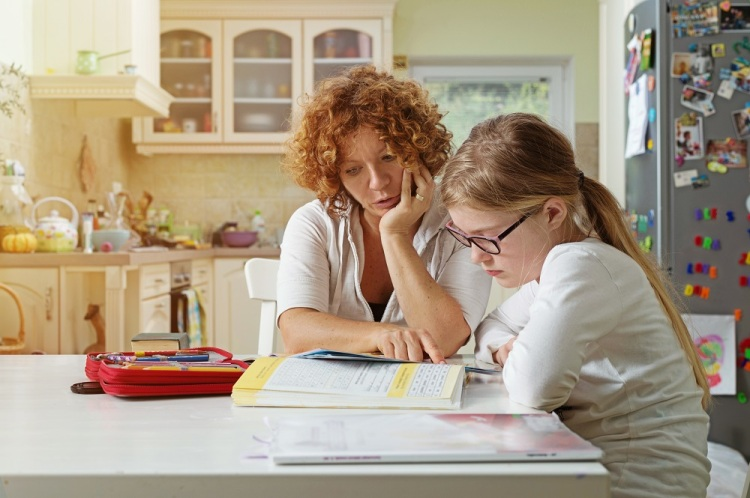 Mother helping daughter at Home Schooling during self isolation period amid coronavirus pandemic..